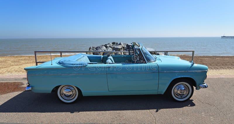 Klassikern tänder - den blåa bilen för den Hillman toppna slynamotorn som parkeras på sjösidapromenad royaltyfri bild
