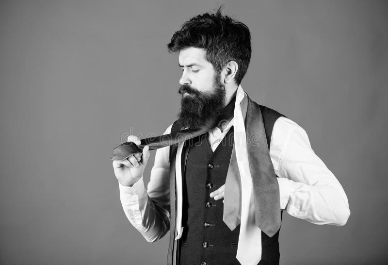 Klassische Art Wie man Krawatte mit Hemd und Anzug zusammenbringt B?rtiger Hippie-Griff des Mannes wenige Krawatten auf blauem Hi lizenzfreie stockfotos