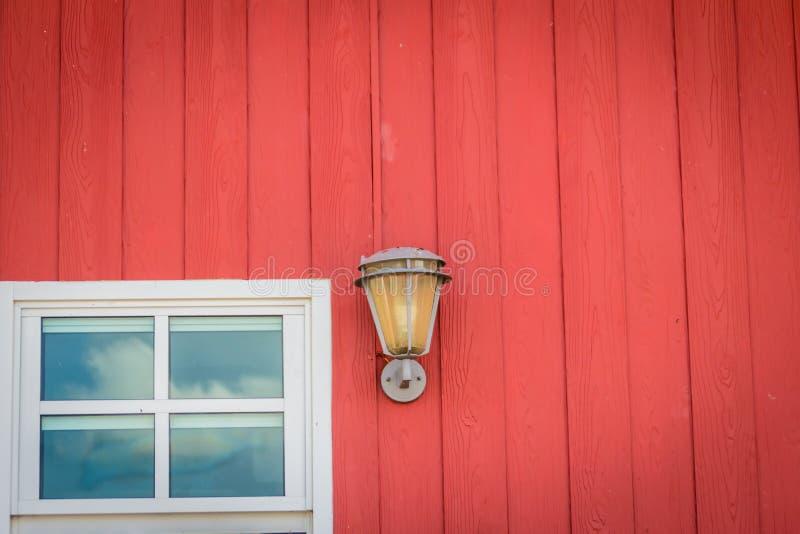 Klassische Designwanddekoration mit Fensterglas und Beleuchtungslampe auf der gemalten roten hölzernen Wand Weinlesemetalllaterne stockbilder