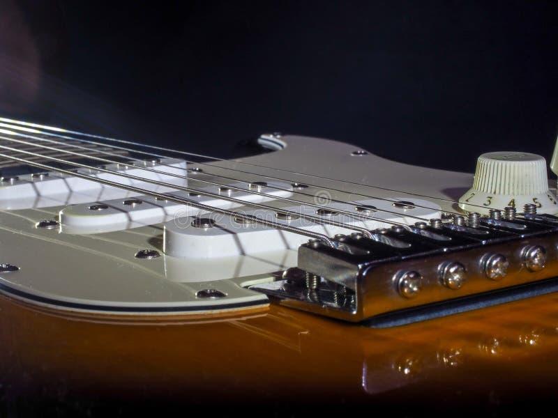 Klassische E-Gitarre der dunkelbraunen Farbe mit Weiß fügt Chromdetails und Eisenschnüre ein stockfotografie