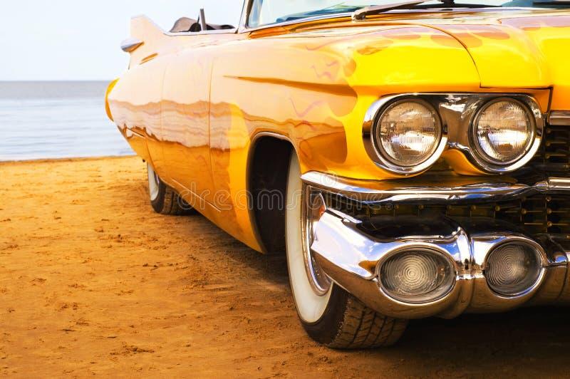Klassische gelbe Flamme gemalter Cadillac am Strand lizenzfreie stockfotografie
