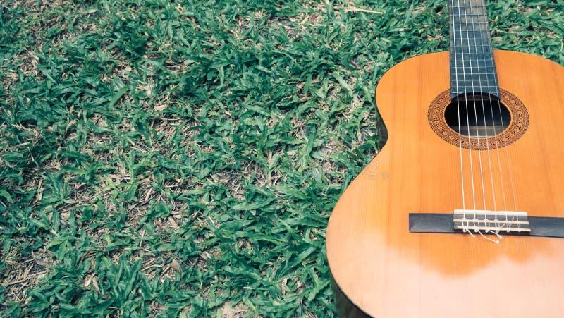 Klassische Gitarre auf dem dunkelgrünen Gras mit Kopienraum stockbild