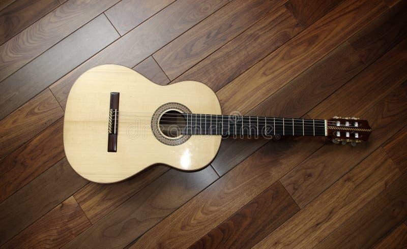 Klassische Gitarre auf hölzernem Hintergrund lizenzfreie stockfotos