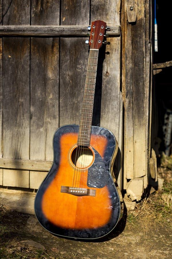 Klassische Gitarre, die an der Holztür sich lehnt lizenzfreies stockfoto