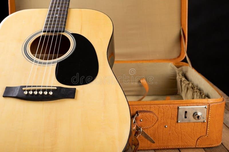 Klassische Gitarre und Koffer auf einem dunklen Holztisch Aufgereihtes Musikinstrument unterwegs stockfoto