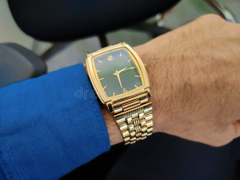 Klassische goldene Uhr an Hand lizenzfreie stockbilder