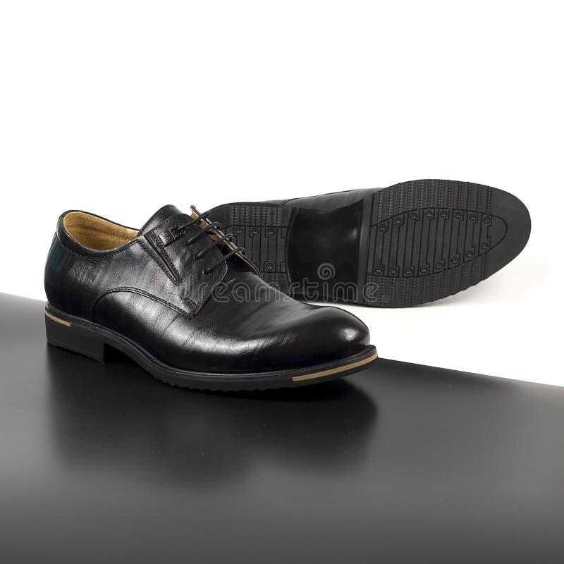 Klassische männliche schwarze Lederschuhe lokalisiert auf einem weißen und ein schwarz lizenzfreie stockfotos
