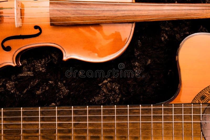 Klassische nahe hohe Ansicht der Gitarre und der Violine über dunklen Hintergrund stockfoto