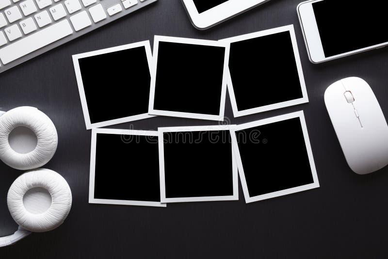 Klassische Papierfotorahmen, Handy, Tablette, Computertastatur und Maus auf grauer Tabelle stockfotos