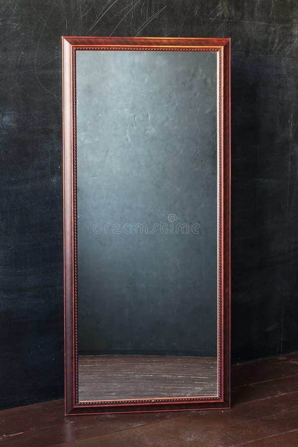 Klassische rechteckige Spiegel withot Reflexion, die im leeren Raum mit schwarzer Wand steht stockfoto