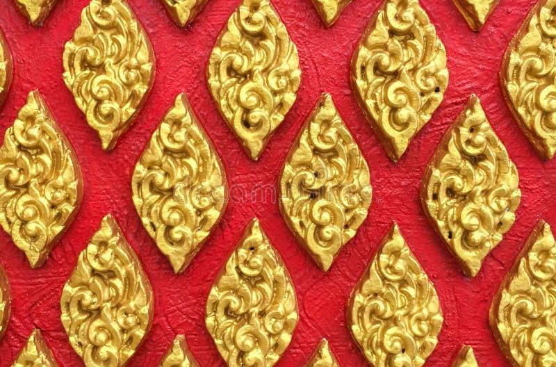 Klassische Steincarvings-thailändische Weinlese-Art-Kunst des goldenen nahtlosen mit Blumenmusters auf der roten konkreten Hinter lizenzfreies stockbild