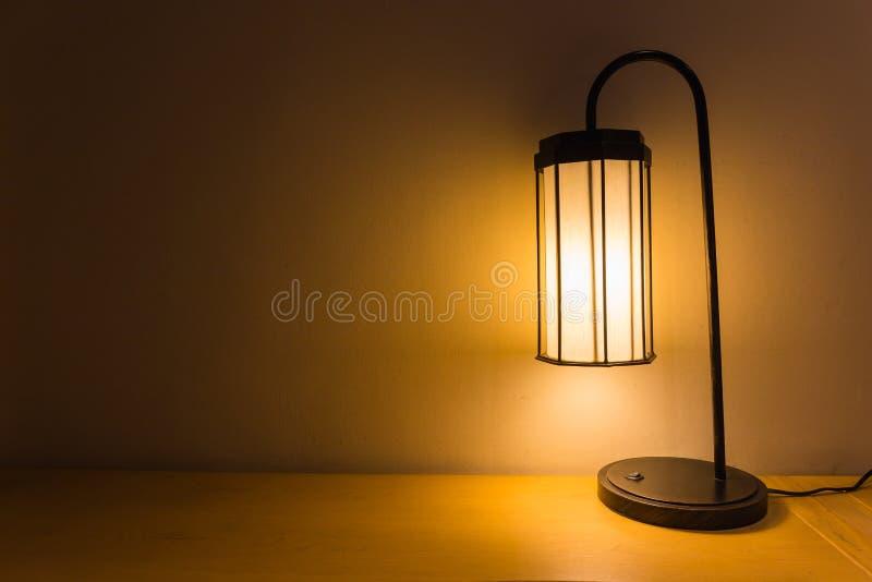 Klassische Tischlampe auf hölzerner Wand und Tabelle lizenzfreie stockbilder
