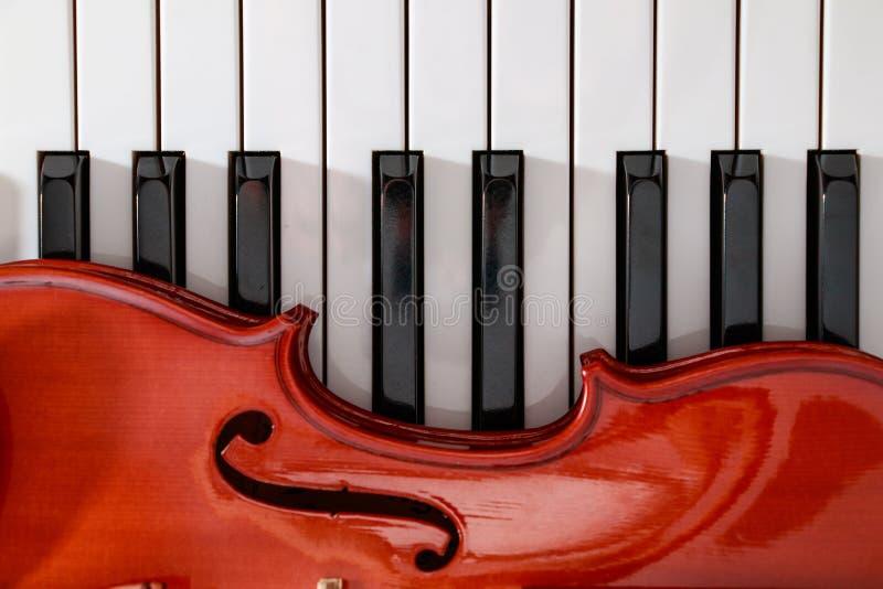 klassische Violine auf weißem und schwarzem Klavier befestigt Nahaufnahmehintergrund lizenzfreie stockbilder