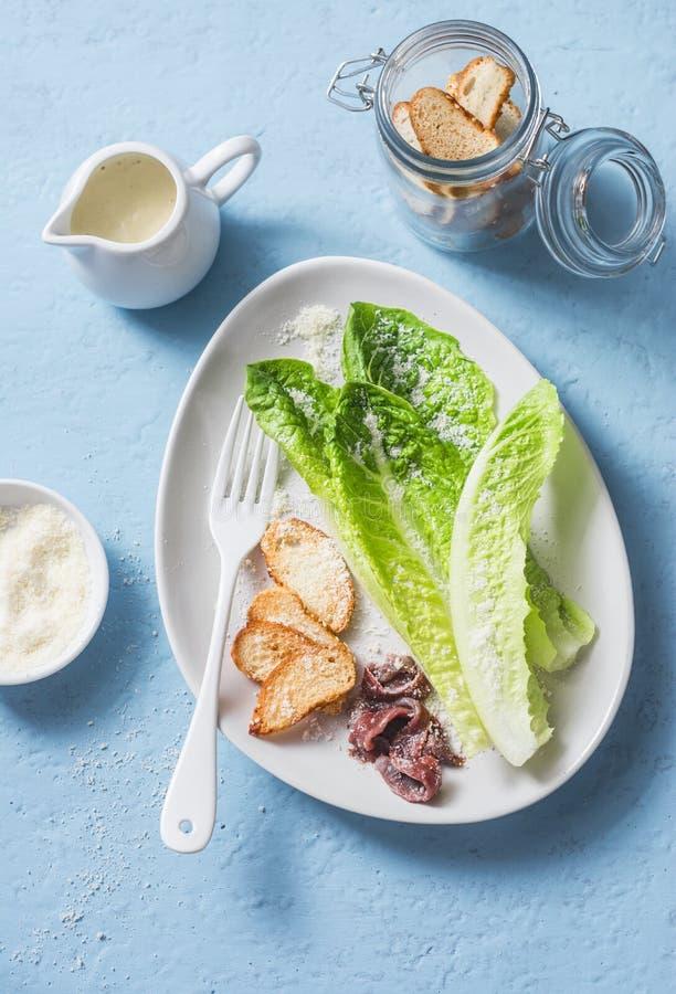 Klassischer Caesar-Salat Romanosalat mit den Sardellen, Parmesankäse, Croutons und Caesar, die auf einem blauen Hintergrund ankle stockfotografie