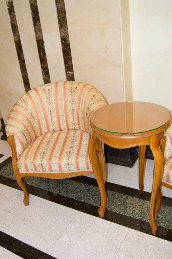 Klassischer eleganter Lehnsessel und ein kleiner Holztisch mit den gebogenen Beinen, hergestellt im Weinleseretrostil, im Marmorb lizenzfreies stockfoto