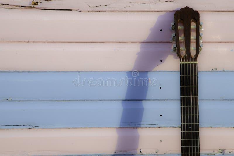 Klassischer Gitarrenhals gegen Pastellrosa und Blau setzt Hütte auf den Strand stockfotografie