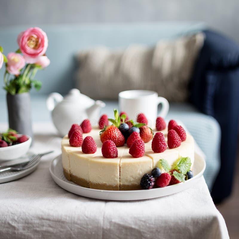 Klassischer Käsekuchen mit frischen Beeren auf der grauen Platte bei Tisch Konzept des gesunden organischen Sommernachtischs lizenzfreie stockfotografie
