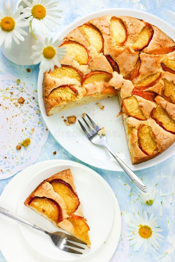 Klassischer Kuchen mit frischen Pfirsichen auf einem blauen Hintergrund mit Blume lizenzfreies stockbild