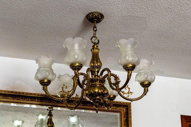 Klassischer Leuchter von der weißen Decke mit Spiegel und von den weißen Wänden lizenzfreies stockfoto