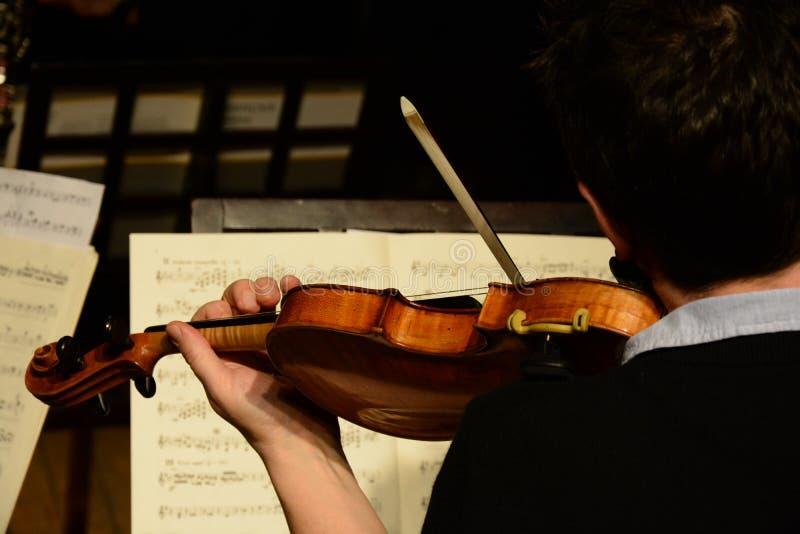 Klassischer Musiker, der die Violine spielt und Musikanmerkungen liest lizenzfreies stockbild