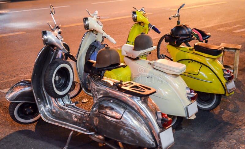 Klassischer Roller am Abend auf der Straße Drei Jahrgangsschotter, schwarz, weiß und gelb Abendfotografie lizenzfreie stockfotografie