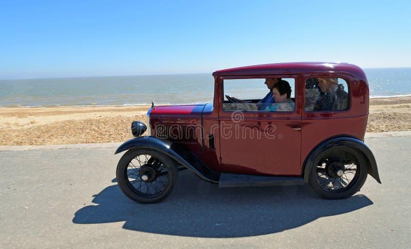 Klassischer roter Austin Seven Car, der entlang Seeseite-Promenade gefahren wird lizenzfreies stockbild