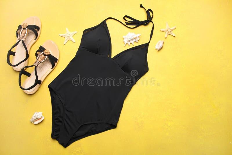 Klassischer schwarzer Badeanzug, Sommersandalen und Marinedekor stockfoto