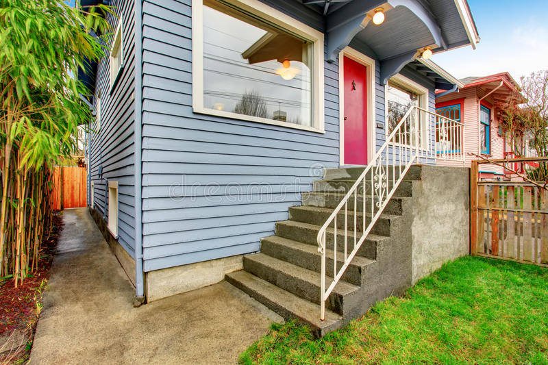 Klassisches amerikanisches Haus außen mit blauer Ordnung und roter Haustür lizenzfreie stockfotos