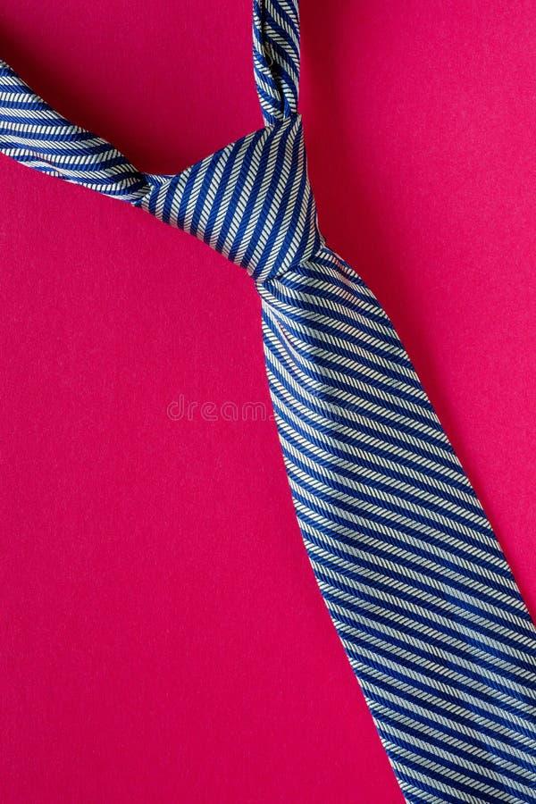 Klassisches Blau gestreifte Bindung auf rotem Hintergrund stockfoto