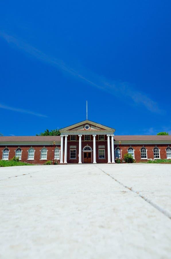 Klassisches Gebäude des roten Backsteins mit griechischem weißem Spalten-Eingang stockfoto
