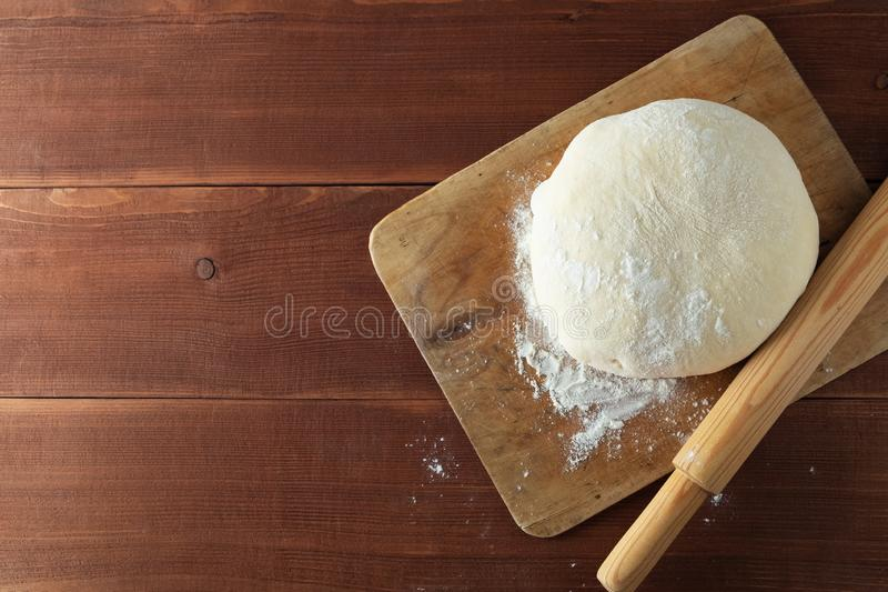 Klassisches hölzernes Nudelholz mit frisch zubereitetem Teig und dem Abwischen des Mehls auf hölzernem Hintergrund stockfotografie