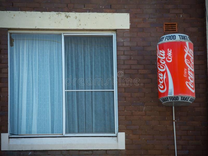 Klassisches Logo Coca-Colas auf dem großen Koks kann modellieren befestigt zum Lebensmittelgeschäftbürogebäude nahe dem Fenster f lizenzfreie stockbilder