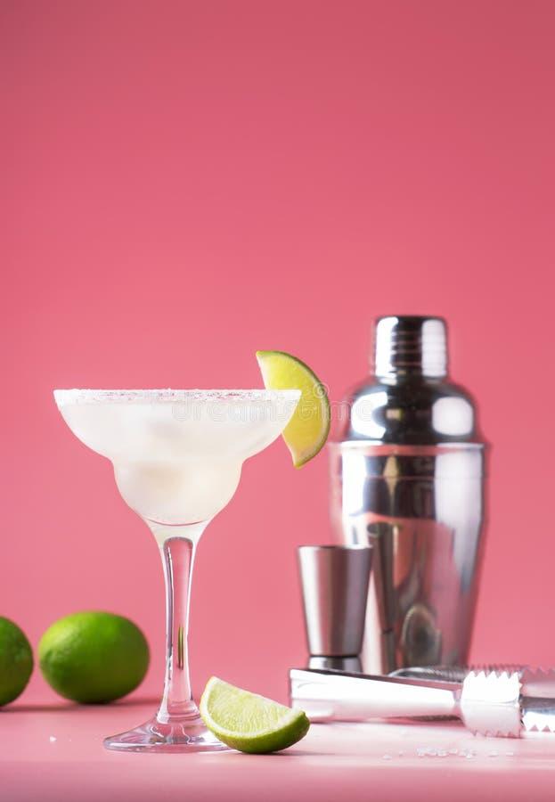 Klassisches Margaritaalkoholcocktail mit Tequila, Likör, Limettensaft, Zuckersirup, Salz und Eis, rosa Hintergrund des Sommers, P stockfotos
