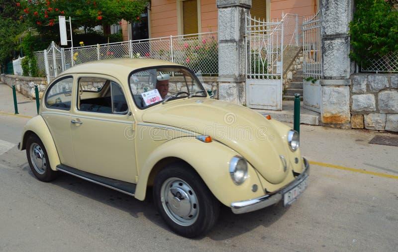 Klassisches Sahne-Volkswagen Beetle-Auto, das entlang Straße gefahren wird lizenzfreie stockfotos