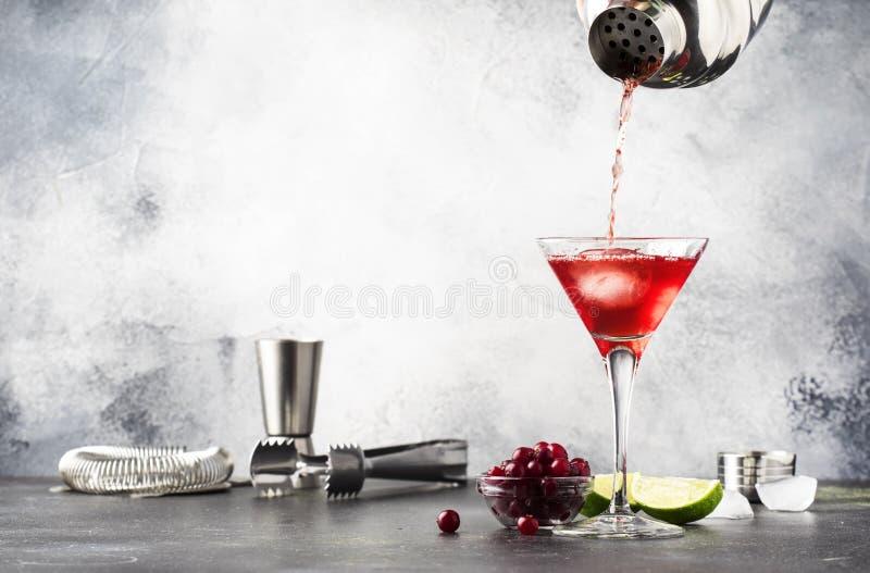 Klassisk alkoholiserad coctail för förberedelse som är cosmpolitan med vodka, likör, tranbärfruktsaft, limefrukt, is och orange p arkivfoto
