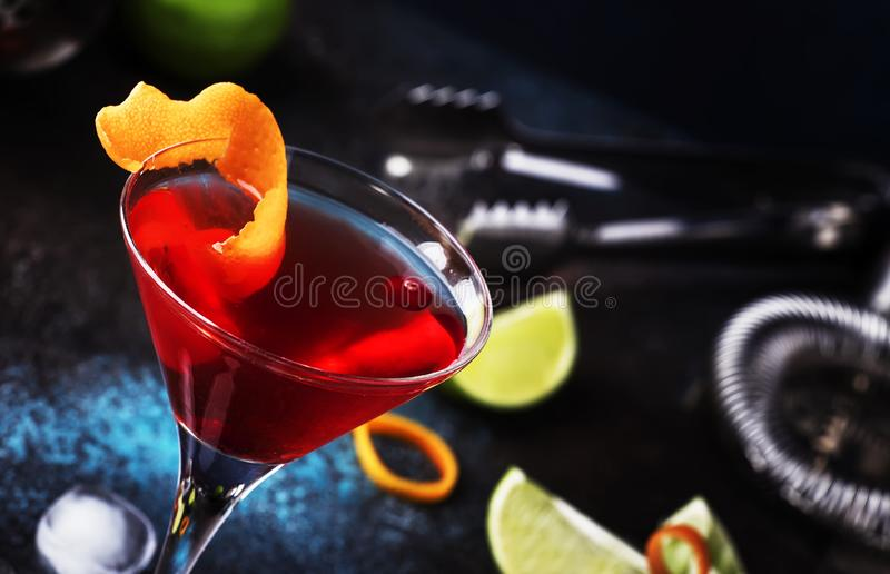 Klassisk alkoholiserad coctailkosmopolit med vodka, likör, tranbärfruktsaft, limefrukt, is och orange piff, mörk stångräknare arkivfoton