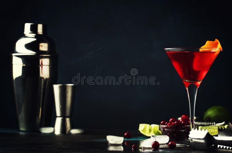 Klassisk alkoholiserad coctailkosmopolit med vodka, likör, tranbärfruktsaft, limefrukt, is och orange piff, mörk stångräknare arkivbilder