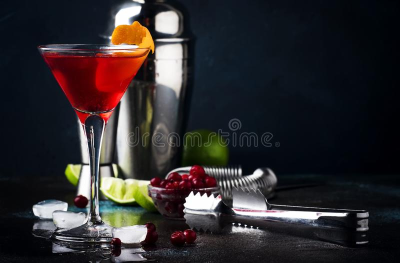 Klassisk alkoholiserad coctailkosmopolit med vodka, likör, tranbärfruktsaft, limefrukt, is och orange piff, mörk stångräknare royaltyfria bilder