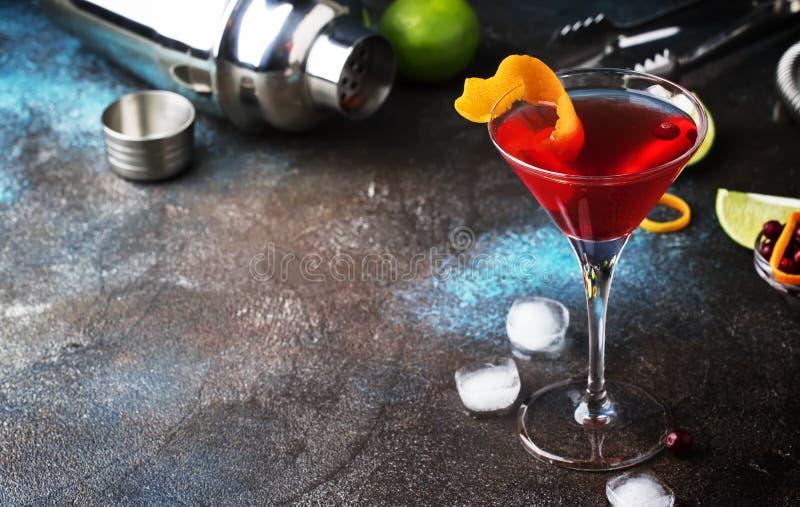 Klassisk alkoholiserad coctailkosmopolit med vodka, likör, tranbärfruktsaft, limefrukt, is och orange piff, mörk stångräknare royaltyfri bild