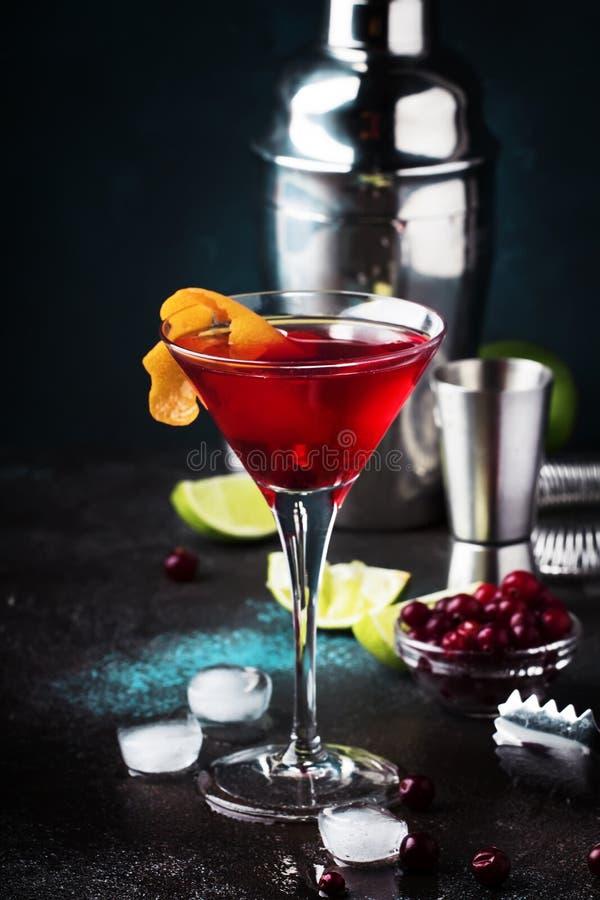 Klassisk alkoholiserad coctailkosmopolit med vodka, likör, tranbärfruktsaft, limefrukt, is och orange piff, mörk stångräknare arkivfoto