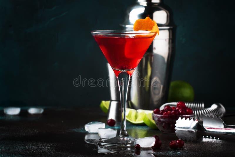 Klassisk alkoholiserad coctailkosmopolit med vodka, likör, tranbärfruktsaft, limefrukt, is och orange piff, mörk stångräknare fotografering för bildbyråer