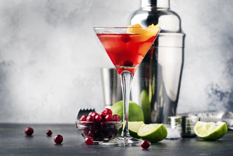 Klassisk alkoholiserad coctailkosmopolit med vodka, likör, tranbärfruktsaft, limefrukt, is och orange piff, räknare för grå stång royaltyfri foto