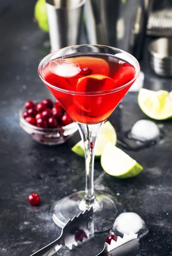 Klassisk alkoholiserad coctailkosmopolit med vodka, likör, tranbärfruktsaft, limefrukt, is och orange piff, räknare för grå stång royaltyfri fotografi