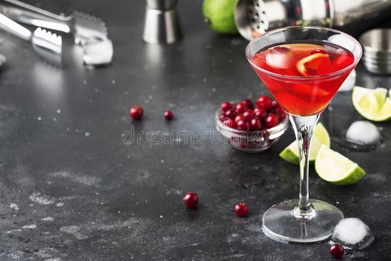 Klassisk alkoholiserad coctailkosmopolit med vodka, likör, tranbärfruktsaft, limefrukt, is och orange piff, räknare för grå stång arkivbilder