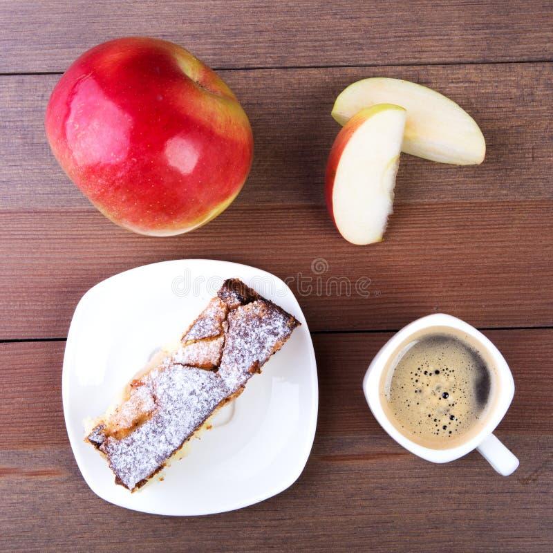 Klassisk amerikansk hemlagad äppelpaj Stycke av den smakliga organiska äppelpajen och koppen med espressokaffe Efterr?tt som ?r k royaltyfria bilder