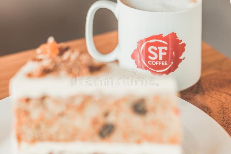 Klassisk amerikansk morot Cake med krämfrostning och en kopp varm latte arkivfoton