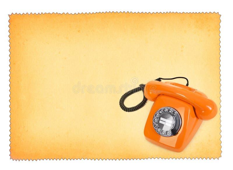 Klassisk bakelitetelefon över nedfläckat papper royaltyfri bild