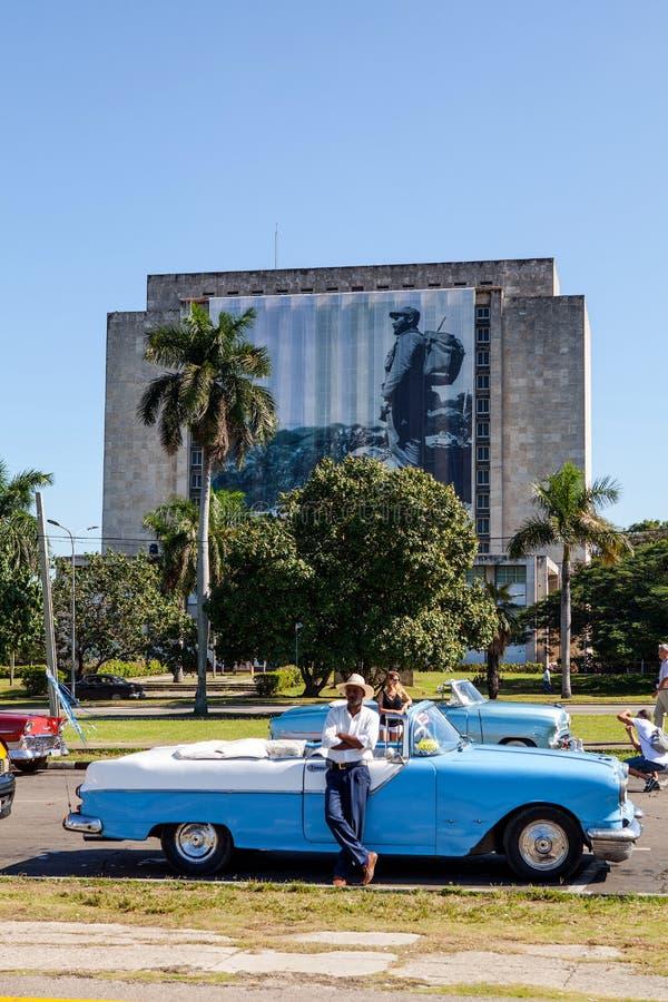 Klassisk biltaxichaufför på Plaza de la Revolucion, Biblioteca Na royaltyfri foto