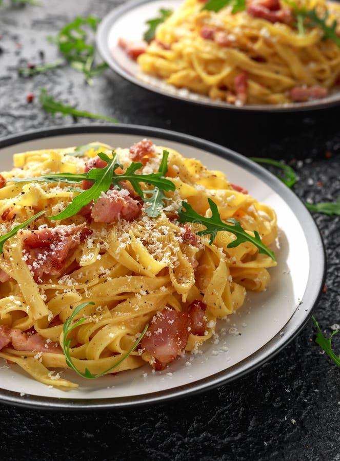 Klassisk Carbonara pasta, spagetti med pancetta, bacon, ägg, parmesanost och grön arugula royaltyfri fotografi