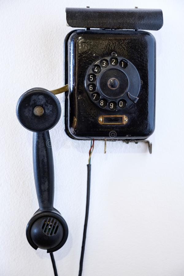 Klassisk gammal telefon på den smutsiga väggen för vit tappningkommunikationsnätverk arkivbilder